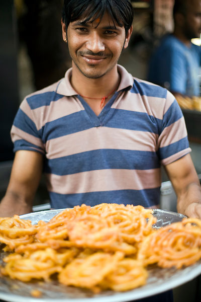 India - Delhi - A man with a tray of fresh jalebi at the Old and Famous Jalebi Wala