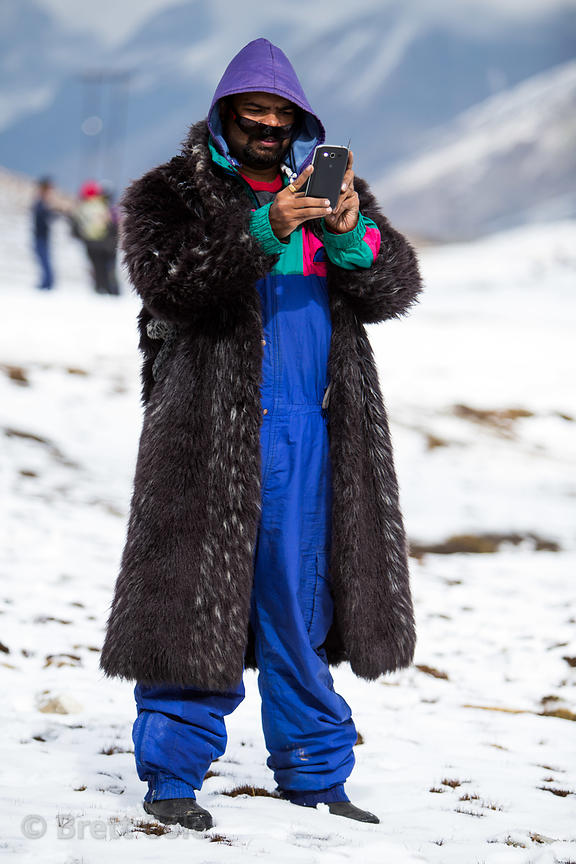 An Indian tourist takes photos while wearing a rented fur coat, at Snow Point on the summit of Rohtang Pass, Manali, India