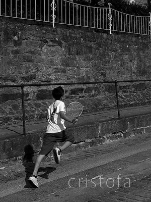boy with tennis racket running