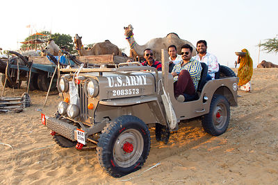 "Tourists drive a ""US Army"" jeep in the desert at the Pushkar Camel Fair, Pushkar, Rajasthan, India"