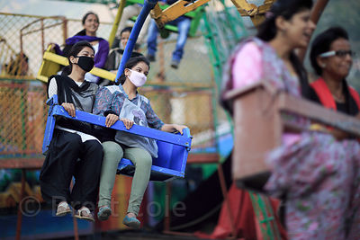 Girls ride a carnival ride while wearing facemasks to protect from air pollution, Kullu, India