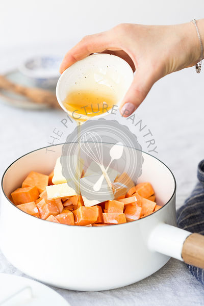 A woman's hand is photographed as she is drizzling maple syrup into sweet potato and butter mixture.