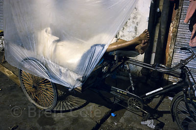 A cycle cart driver in sleeps in his cart in the Paharganj area of Delhi, India. A large percent of rickshaw and cart drivers...