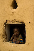 Girl looking through the window of a typical mud house, Matam, Senegal