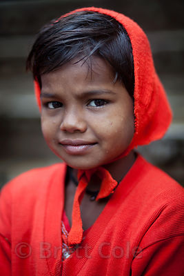 A girl in a bright red bonnet and sweater, Bundi, Rajasthan, India
