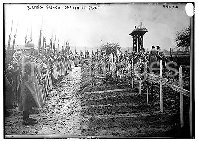 Photograph shows soldiers standing at graves during the burial of a French officer during World War I.