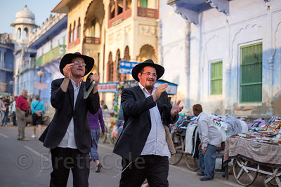 Two orthodox Jewish men sing while walking down main street, Pushkar, Rajasthan, India