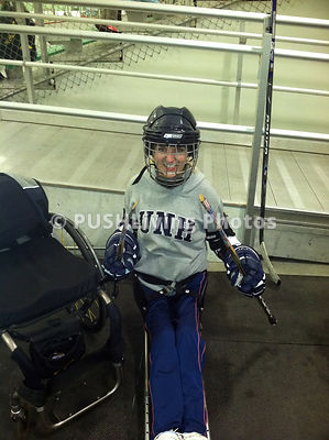 Young woman in an ice hockey sled ready for the rink