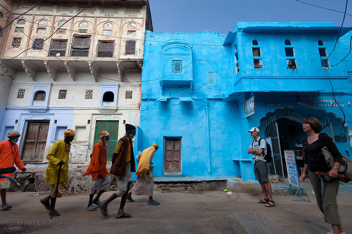 Sadhus walk past a vibrant blue building in Pushkar, Rajasthan, India