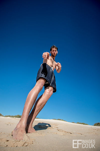 Man Standing On The Sand, Pointing, Low Angle