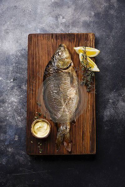 Baked carp with lemon and sauce on cutting board