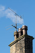 Smoke coming from house chimney with TV aerial attatched. North Yorkshire, UK.
