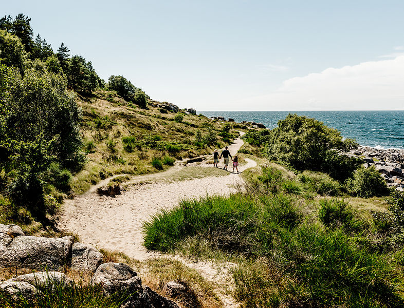 Father and two children walking on Hammerknuden on Bornholm, Denmark