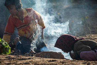 Two children stoke a fire to keep warm in the morning at the Pushkar Camel Mela, Pushkar, India.