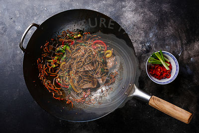 Stir fry noodles Soba with beef and vegetables in wok pan on dark background