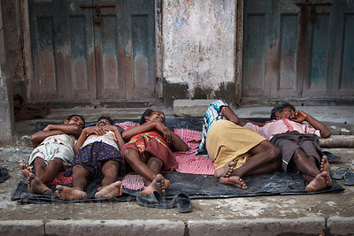 Workers take a siesta on a sidewalk in Kumartoli, Kolkata, India. Sleeping in public is very common in Kolkata.
