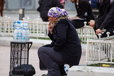Water seller smoking a cigarette