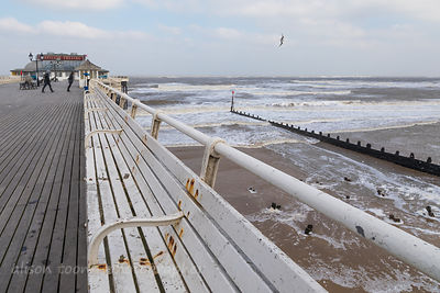 Leaning into the wind on Cromer Pier