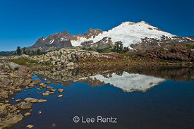 A rock-edged mountain tarn near the trail to Park Butte Lookout with Mt. Baker looming in the distance, Mt. Baker–Snoqualmie ...
