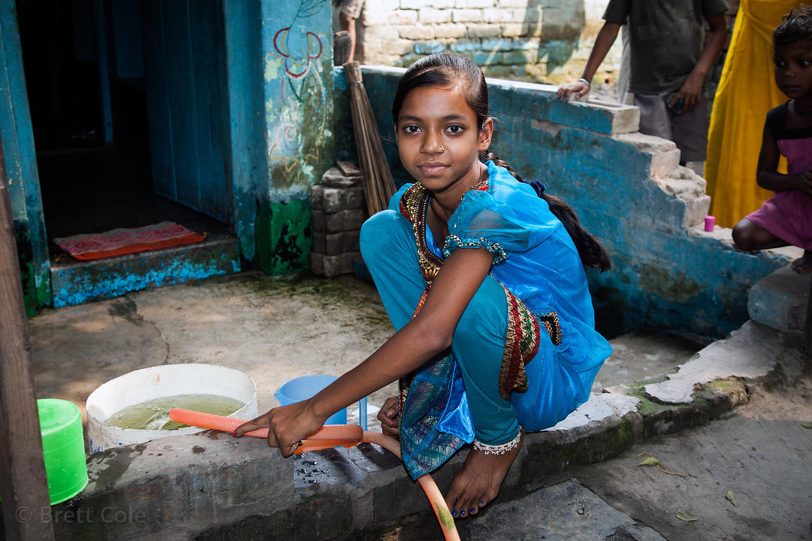 "A girl fills a water bucket in a ""slum"" area in Taratala, Kolkata, India"