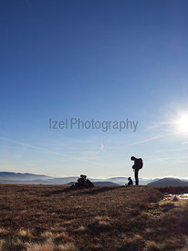 A hiker and their dog on a summit on a cold winters morning in the Derwent Fells, English Lake Distrct, UK.
