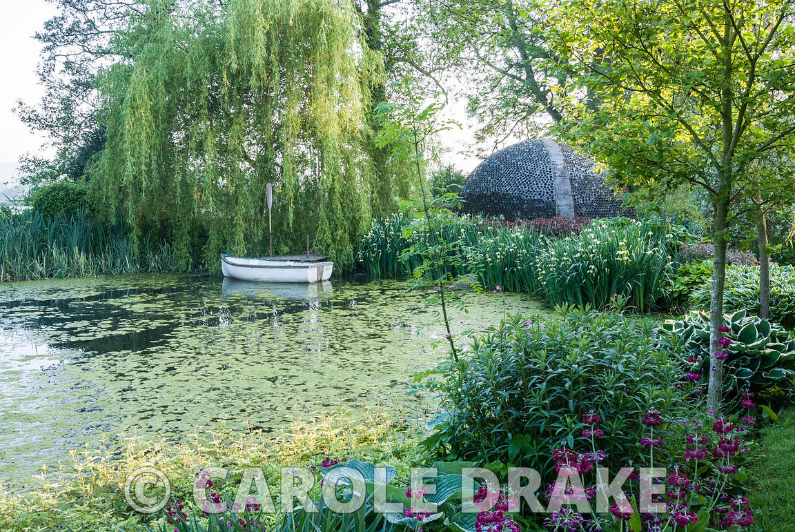Lake edged with hostas and primulas contains small rowing boat below a weeping willow tree, with dome shelter made of glass b...