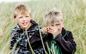 Boys with magnifying glass in the dunes in Thy