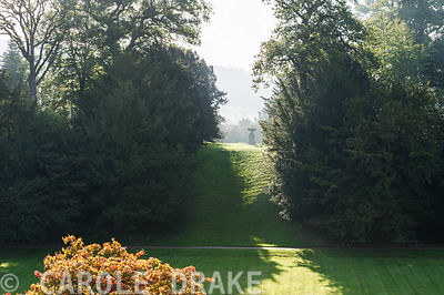 View from the terraces of Powis Castle Garden across the Great Lawn to the tree clad bank beyond, an architectural urn and th...