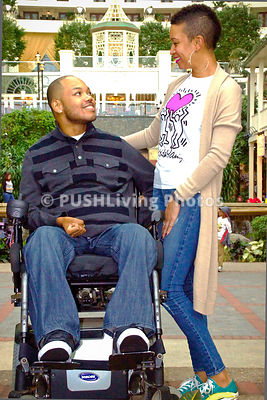 Man using a power wheelchair out with his girfriend in the city