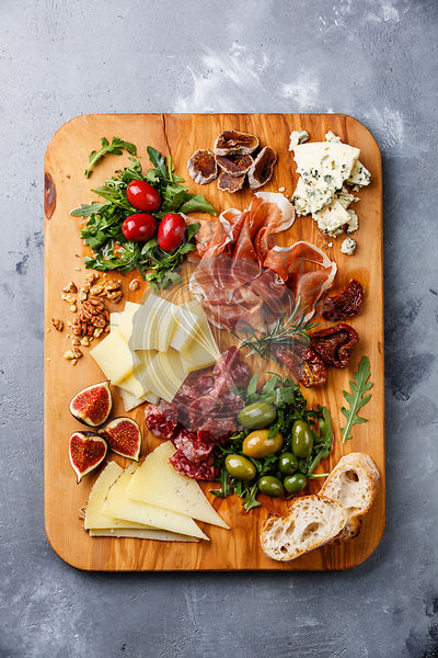 Italian snacks food with Ham, Olive, Cheese, Sun-dried tomatoes, Sausage and Bread on wooden cutting board on concrete backgr...