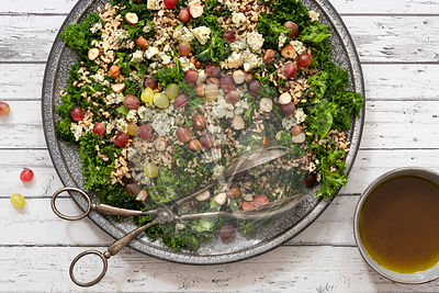 Kale, nut and mixed grain salad with a bowl of spicy dressing.
