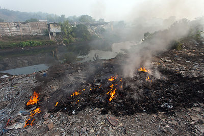Burning piles of scrap metal near Dhapa, Kolkata, India. Dhapa is the site of Kolkata's largest landfill, and numerous recycl...