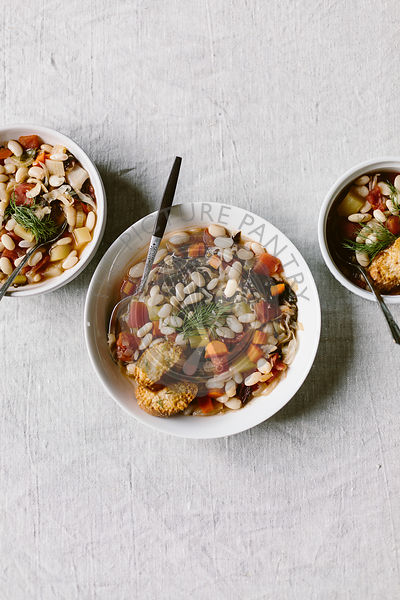3 bowls of Cannelini Bean Soup are photographed from the top view.