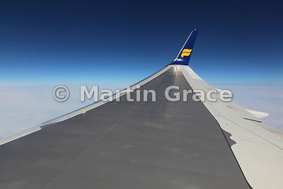 Wing and wingtip of IcelandAir Boeing 757 against dark blue sky