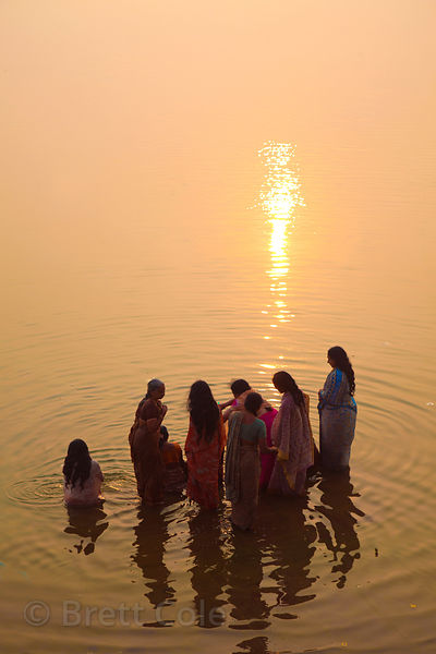 A group of women pray in the Ganges River, Varanasi, India.