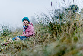 Little Danish girl in a blue hat at the beach in autumn 2