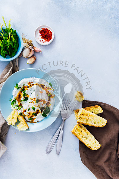 Turkish eggs served in a blue bowl drizzled with a butter sauce accompanied by spinach, red pepper flakes and toasted bread.