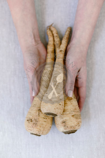 Parsnips being held in a womans hands