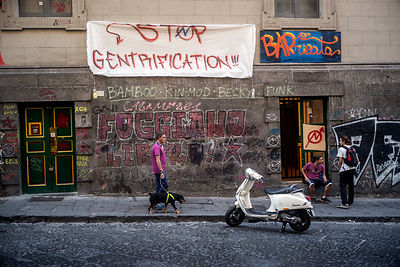 A man walks his dogs past students protesting gentrification in Naples, Italy.