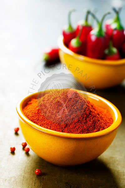 Paprika in a bowl and hot chili peppers