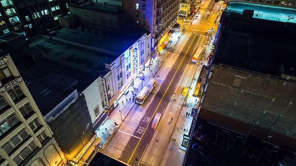 Bird's Eye: Cueing Cars Among Mid-Rises On A Colorful Street At Night
