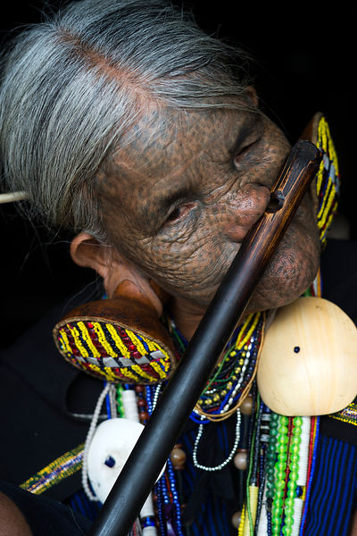 Chin woman playing nose flute