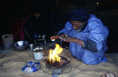 Mauritania - Chinguetti - A nomad makes a fire in the Sahara desert between the cities of Chinguetti and Choum
