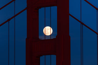 The June full moon rising behind the Golden Gate Bridge, June 6, 2009.  Seen from the Marin Headlands on Conzelman Road.