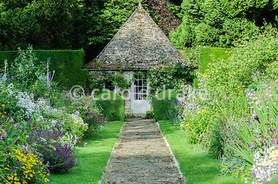 Double herbaceous borders framed with clipped box and tall yew hedges include delphiniums, phlox, campanulas and poppies, and...