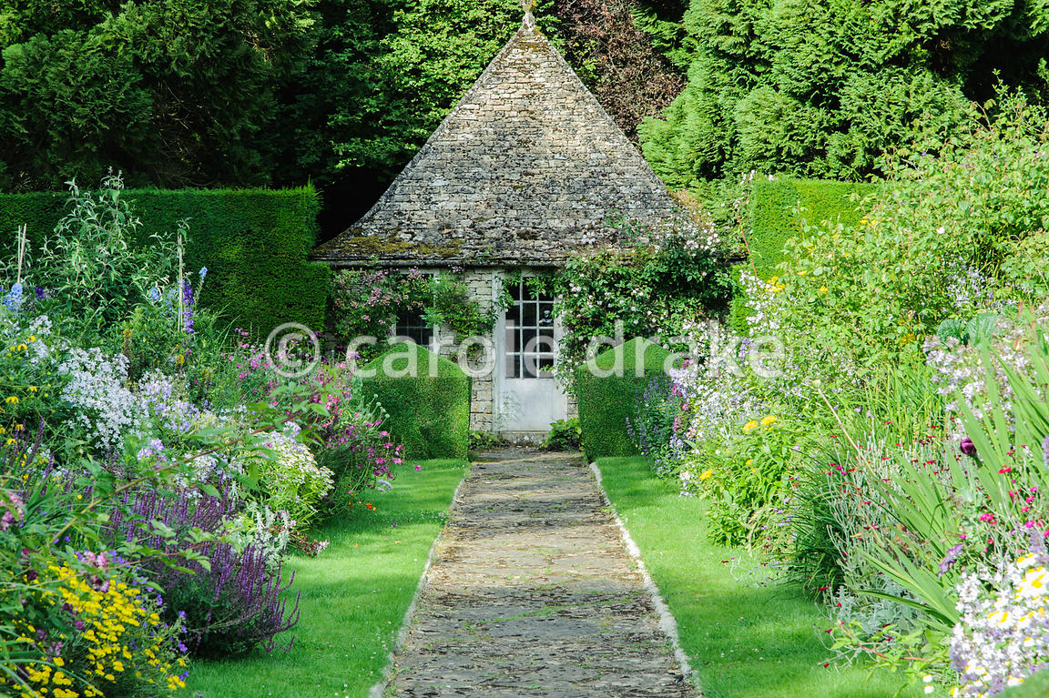 Double herbaceous borders framed with clipped box and tall yew hedges include delphiniums, phlox, campanulas and poppies, and central stone path leading to summerhouse. Rodmarton Manor, Rodmarton, Tetbury, Glos, UK