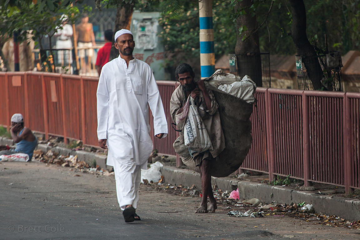A Muslim man passes an impoverished man on the street near Red Road, Kolkata, India.