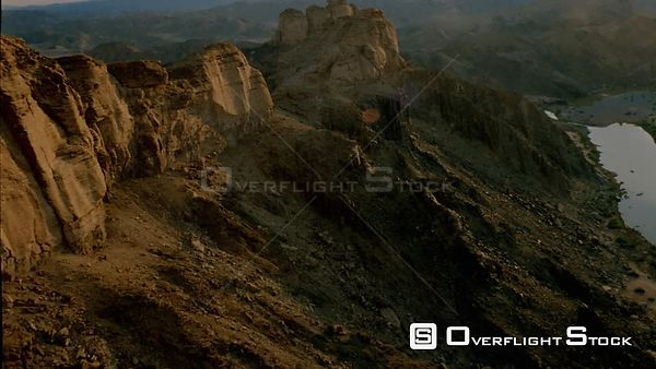 Aerial canted angle wide angle shot side of mountain with cliff face and jagged rocky outcrops, towards and over pinnacle wit...