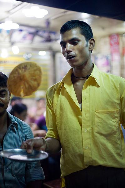 India - Delhi - A waiter flips a cooked paratha on a plate at Parawthe Wala restaurant in Old Delh