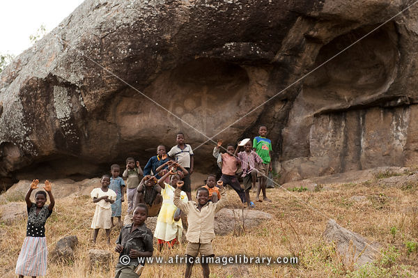 Children in front of an ancient rock painting site, Mphunzi Mountain, near Dedza, Malawi